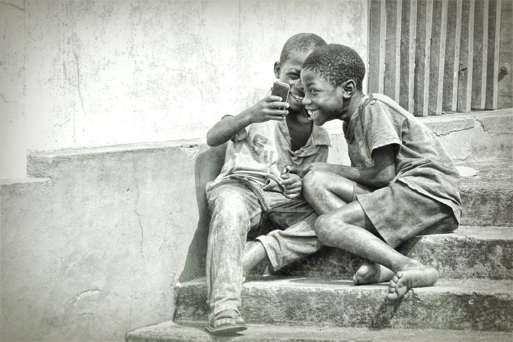 Dois meninos, sentados na escada externa, olhando para um celular que está na mãe de um deles. Ambos sorriem. A foto é TerryWhite e foi feita em Gana.