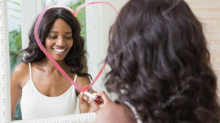 mulher negra se olhando no espelho